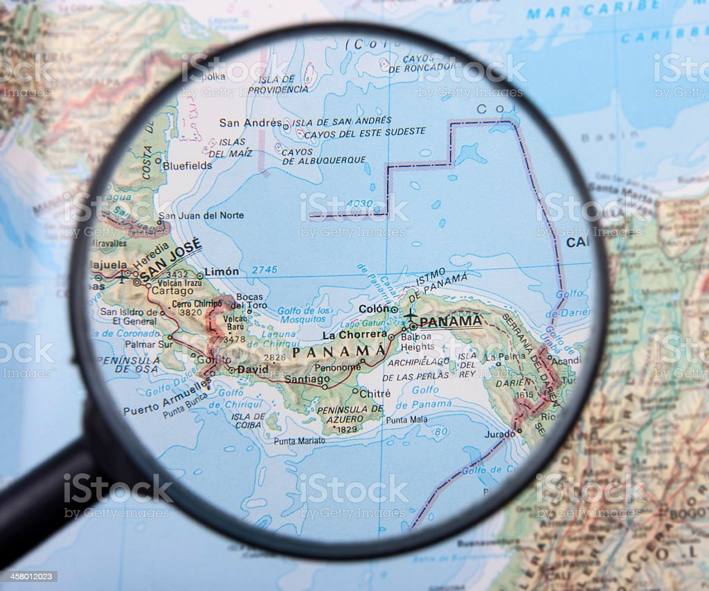 Magnifying glass held over Panama on map stock photo