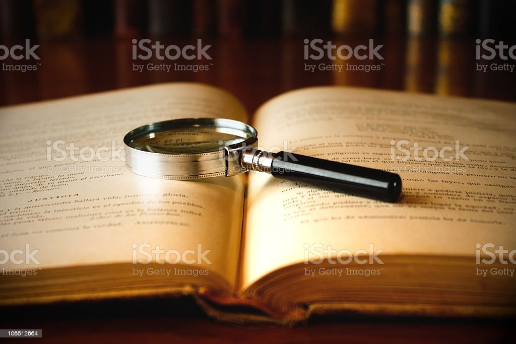 Magnifying glass laid on the open pages of an old book stock photo