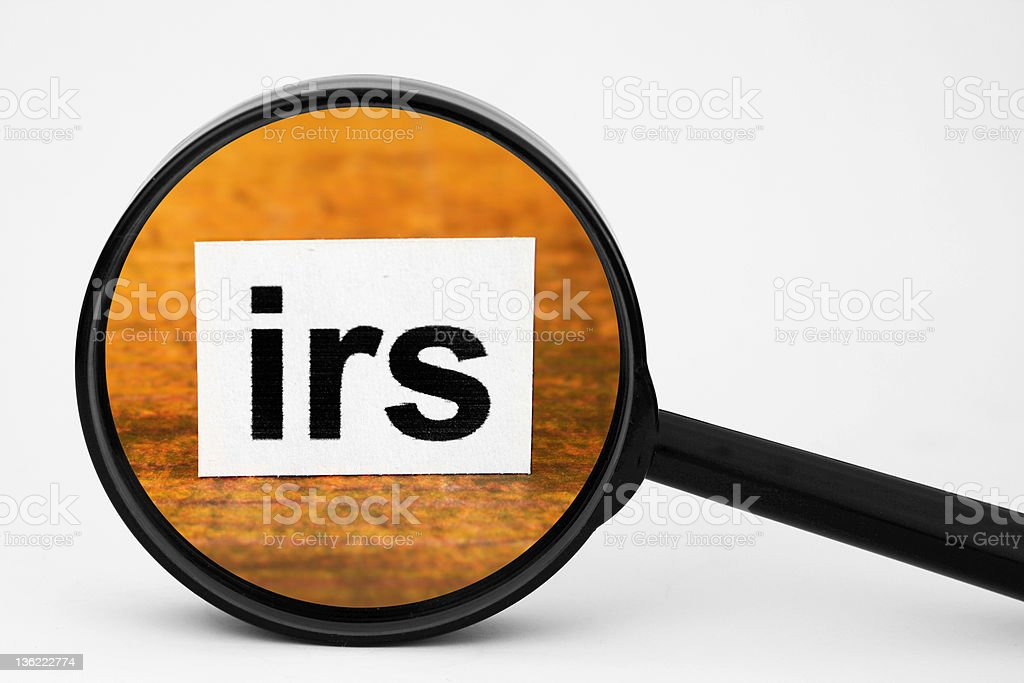 A magnifying glass looking at a label reading IRS stock photo
