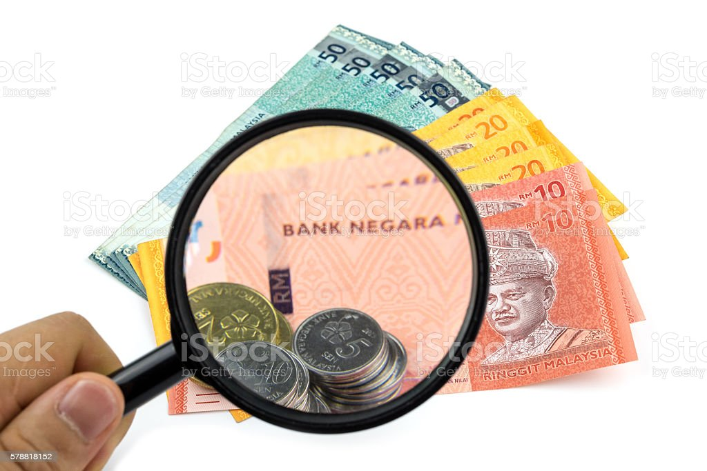 Magnifying glass looking at banknotes and coins on white background stock photo