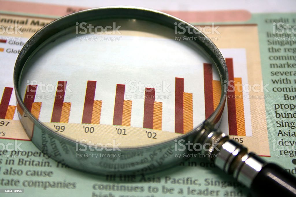 A magnifying glass looking over a set of chart figures royalty-free stock photo