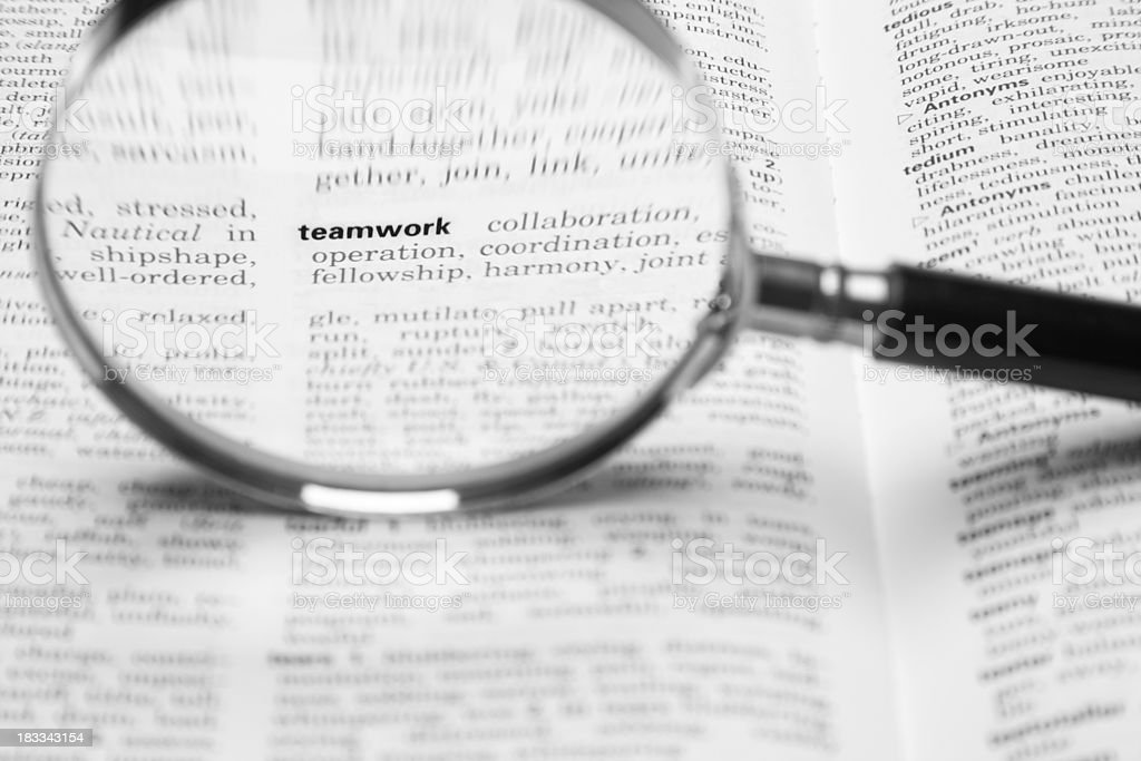 Magnifying glass / loupe (focus on the word teamwork) royalty-free stock photo
