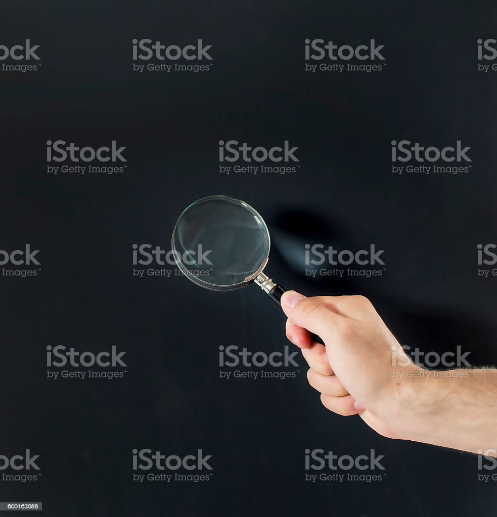 magnifying glass on a black board stock photo