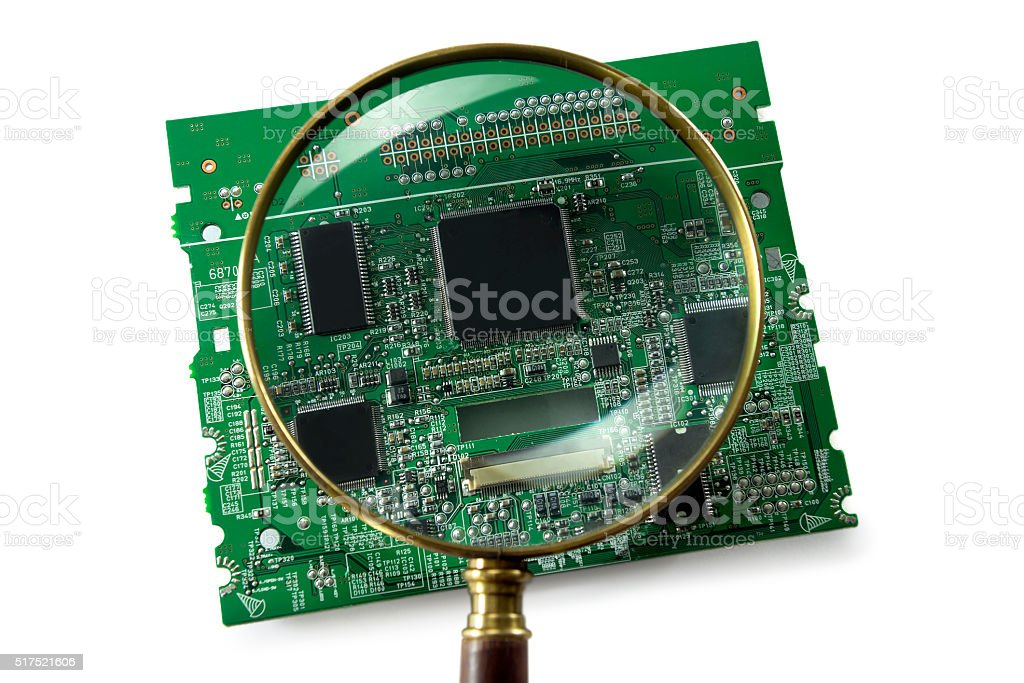 Magnifying glass on a motherboard. Security concept. stock photo