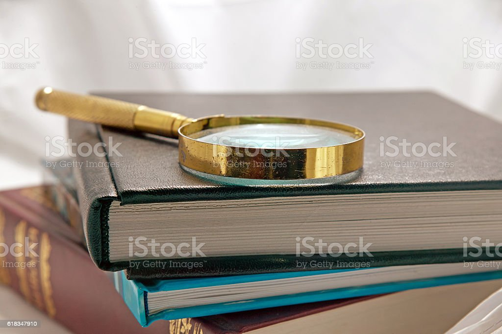 magnifying glass on a stack of books background stock photo