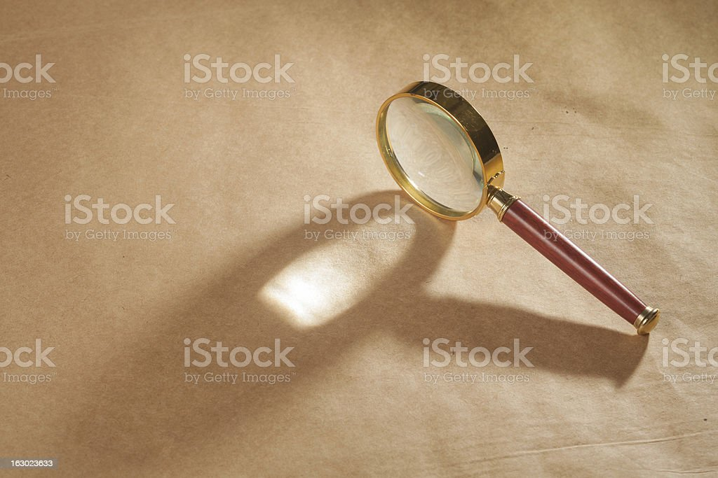 Magnifying Glass on Brown Background royalty-free stock photo