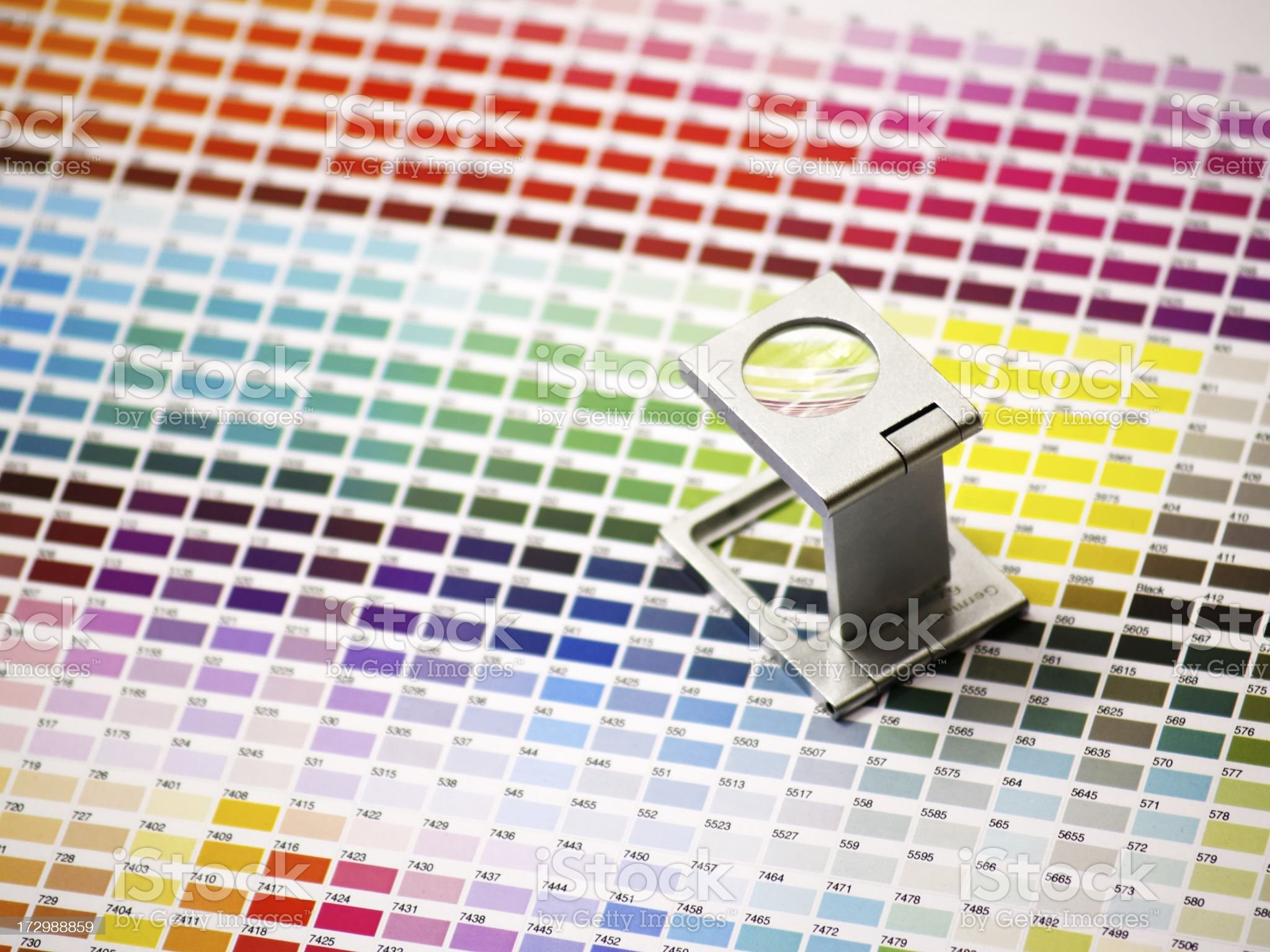 magnifying glass on color tables royalty-free stock photo
