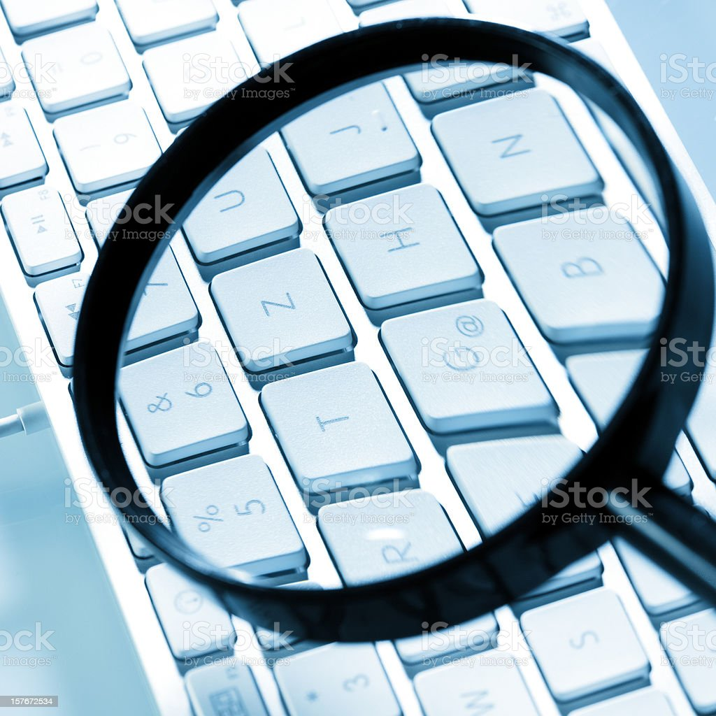 Magnifying glass on computer keyboard royalty-free stock photo