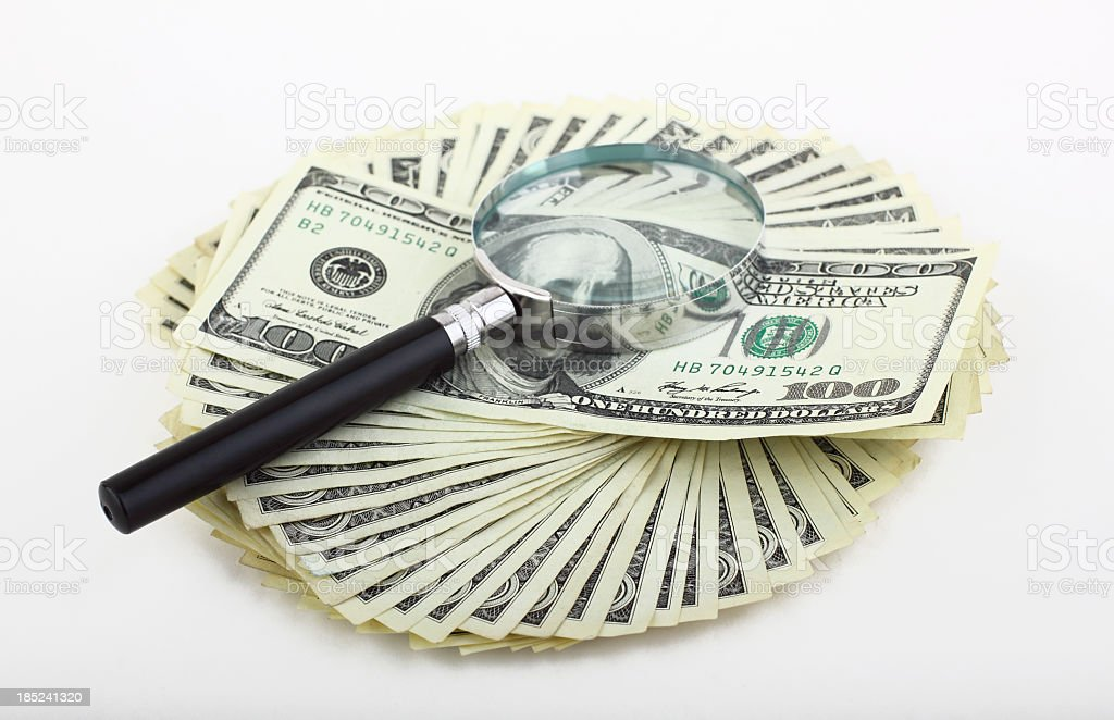 Magnifying glass on dollars royalty-free stock photo