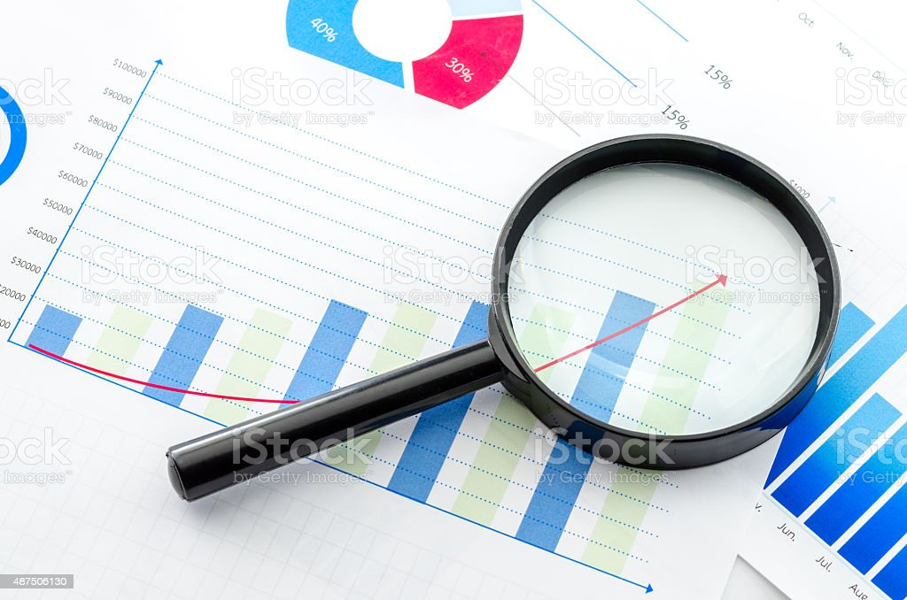 Magnifying glass on financial charts and graphs stock photo