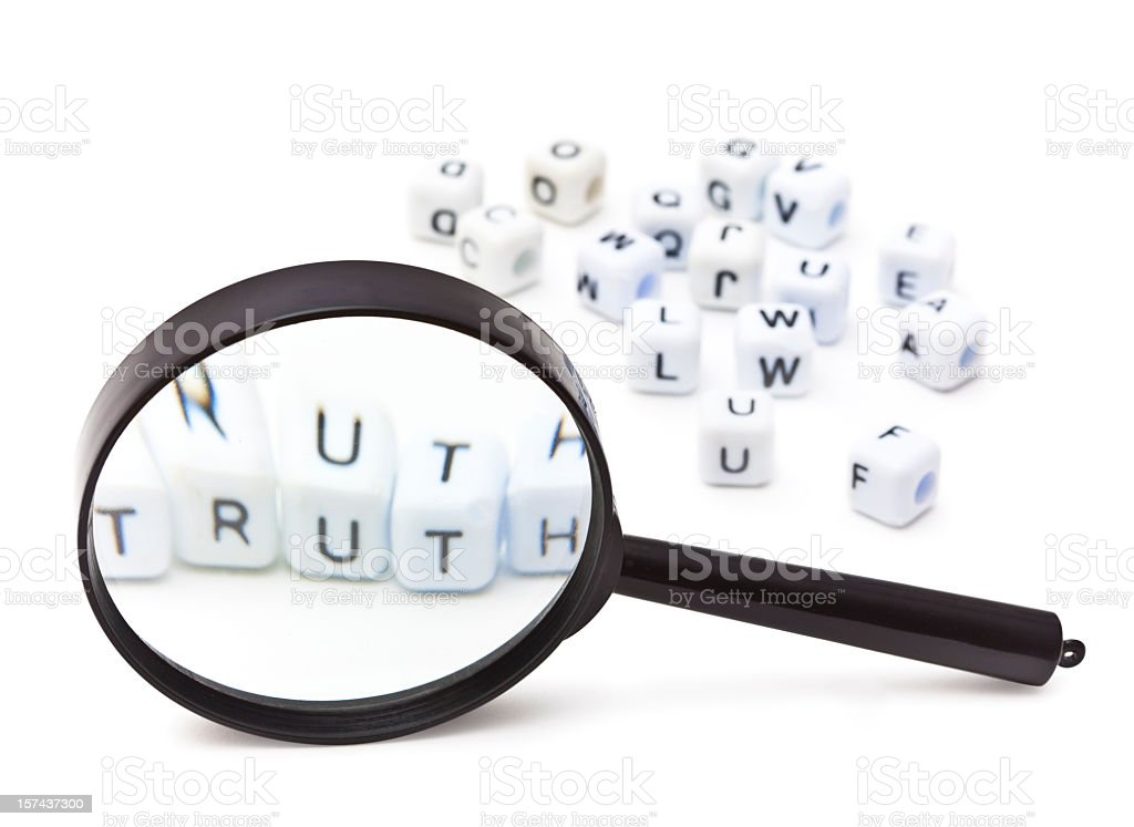 A magnifying glass on letter die, spelling out truth royalty-free stock photo