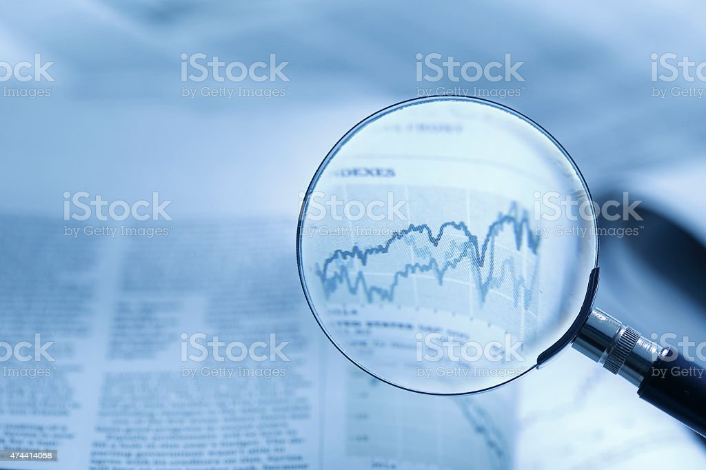 Magnifying glass on line graph stock photo