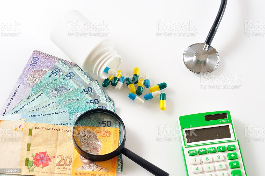 Magnifying Glass On Malaysian Bank Note, Pill, Stethoscope and Calculator stock photo