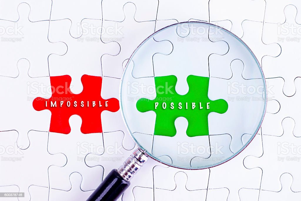 Magnifying glass on missing puzzle  with IMPOSSIBLE AND POSIBBLE stock photo