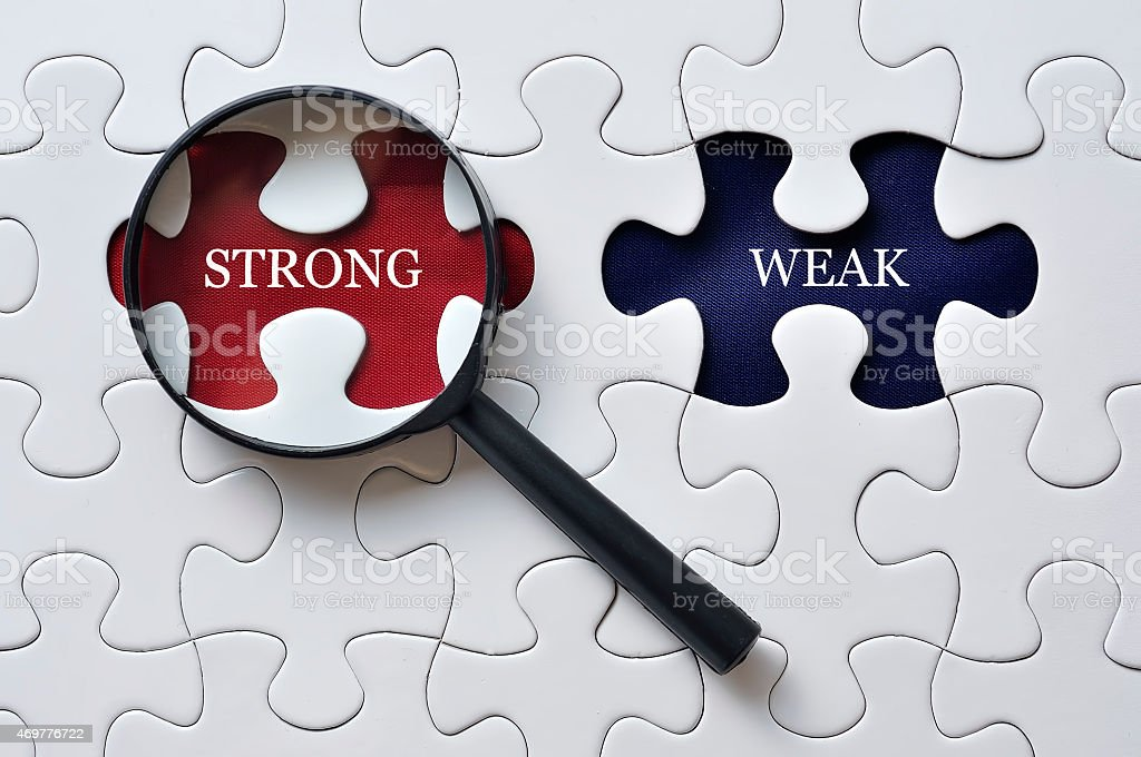 Magnifying Glass On Missing Puzzle with 'STRONG/WEAK' Word, Antonym Concept stock photo