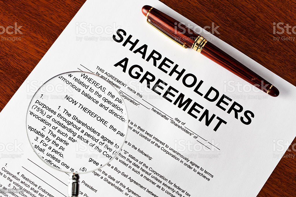 Magnifying glass on shareholders agreement royalty-free stock photo