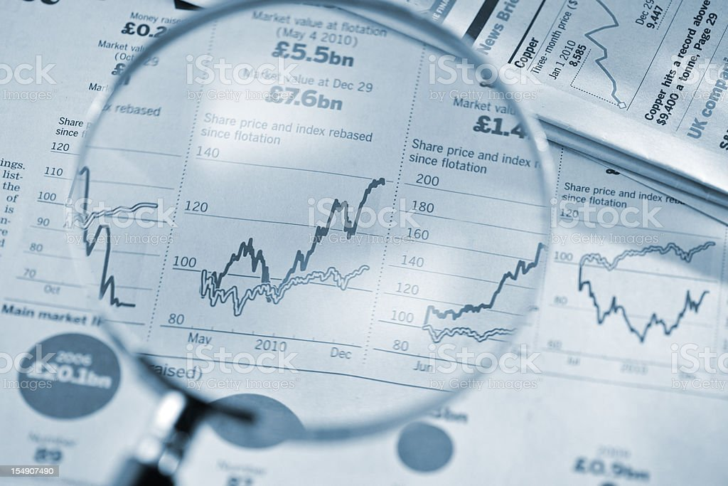 magnifying glass on stock price graphs from financial newspaper royalty-free stock photo