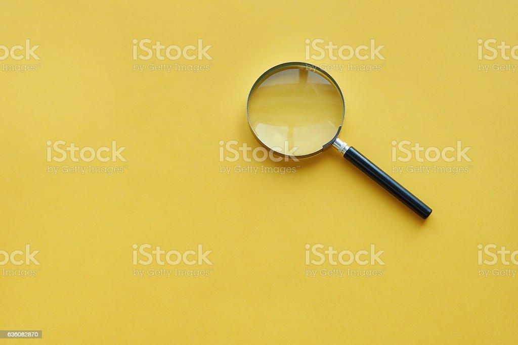 Magnifying glass on the orange background stock photo