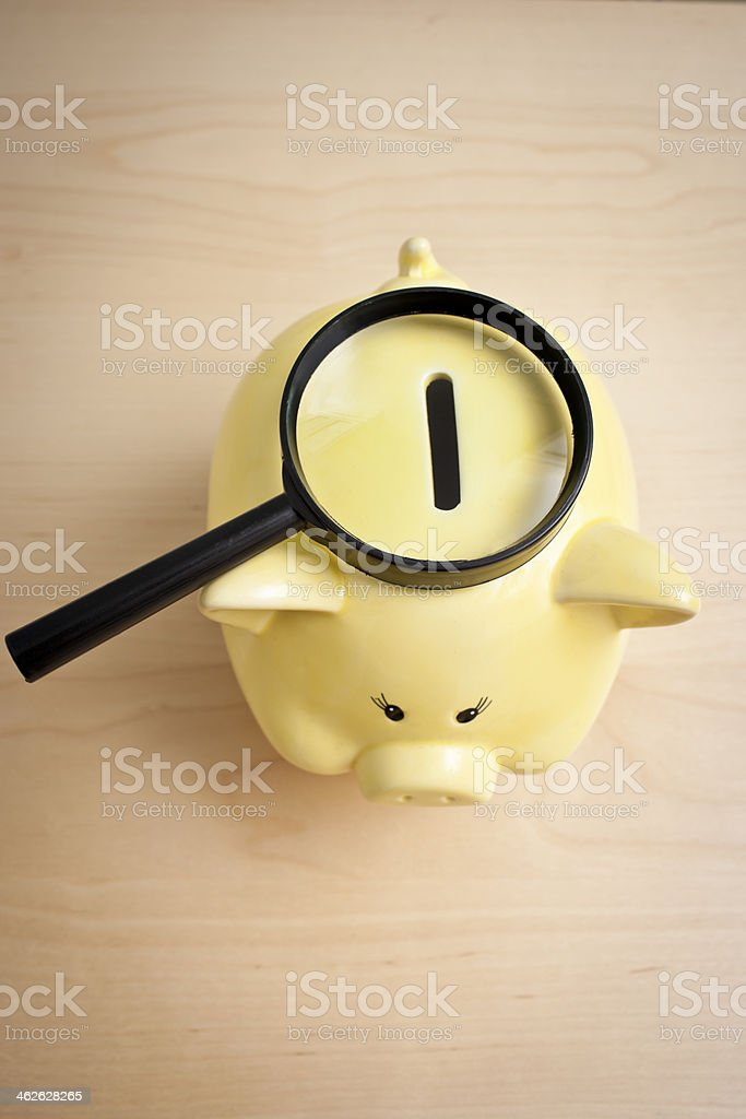 Magnifying glass on top of coin piggy bank in vertical view royalty-free stock photo