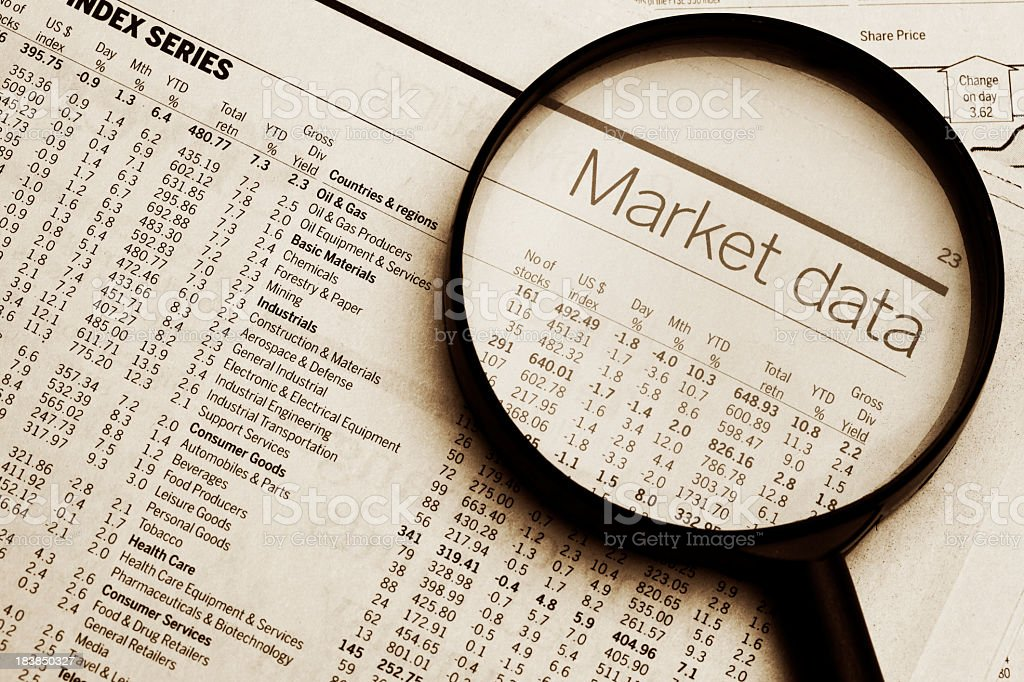Magnifying glass on top of market data document stock photo