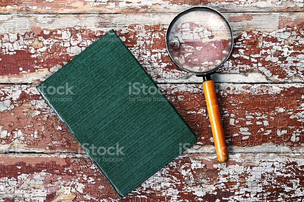 Magnifying glass or loupe with book stock photo