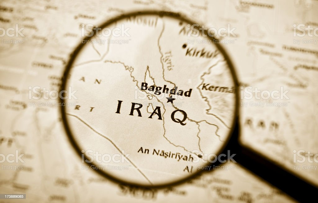 Magnifying glass over a map of Iraq. stock photo