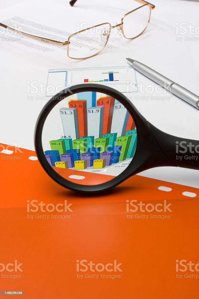 magnifying glass over financial chart and red file stock photo