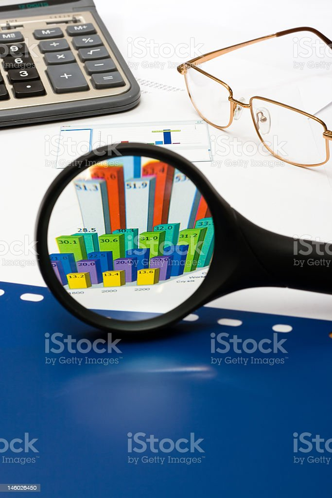 magnifying glass over financial graph royalty-free stock photo