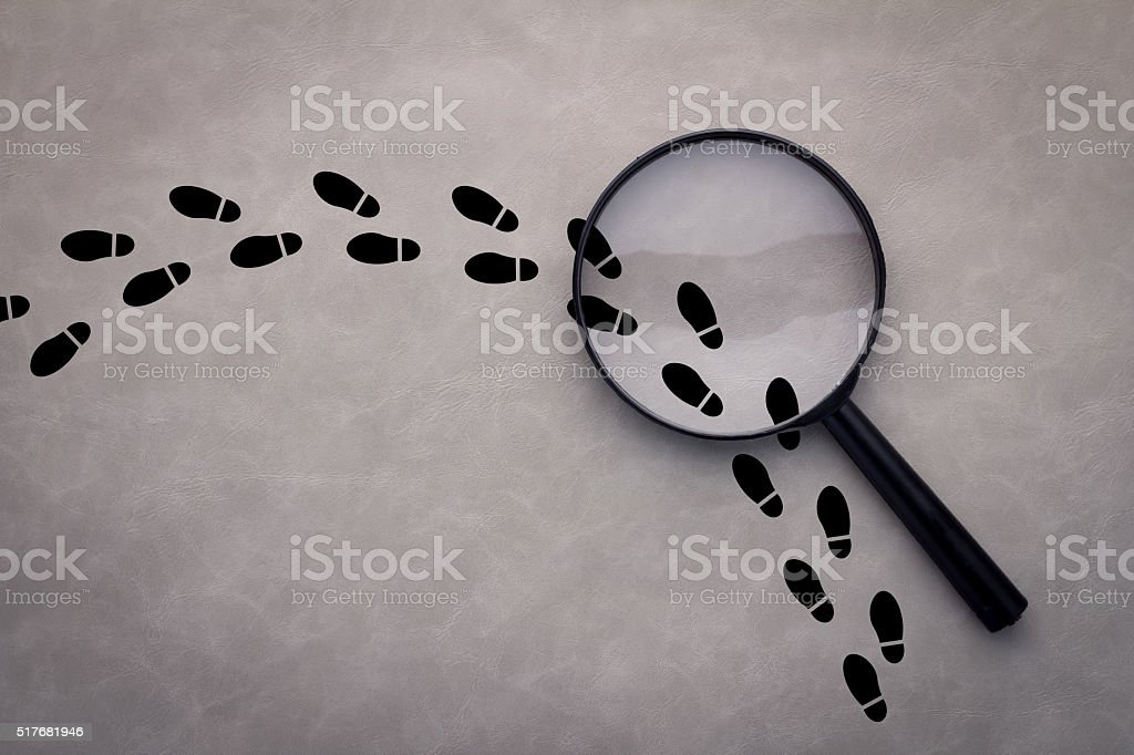 Magnifying glass over footsteps stock photo