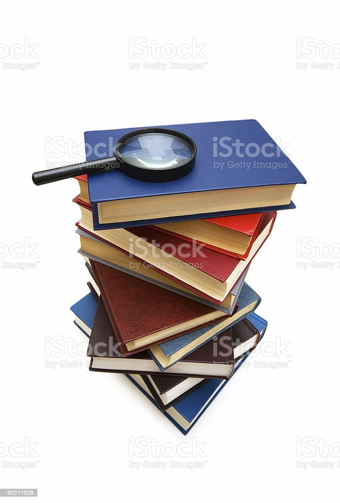 Magnifying glass over the stack of books royalty-free stock photo