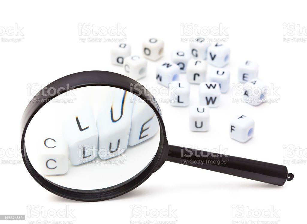 A magnifying glass over the word clue with blocks stock photo