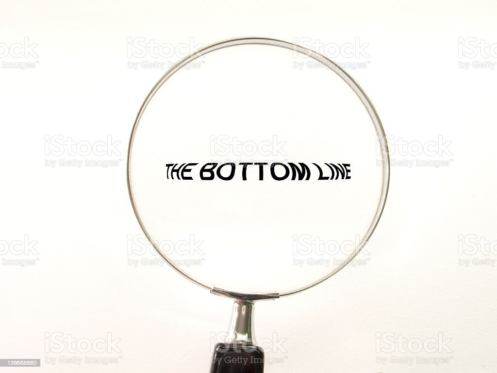 A magnifying glass over the words 'the bottom line' stock photo