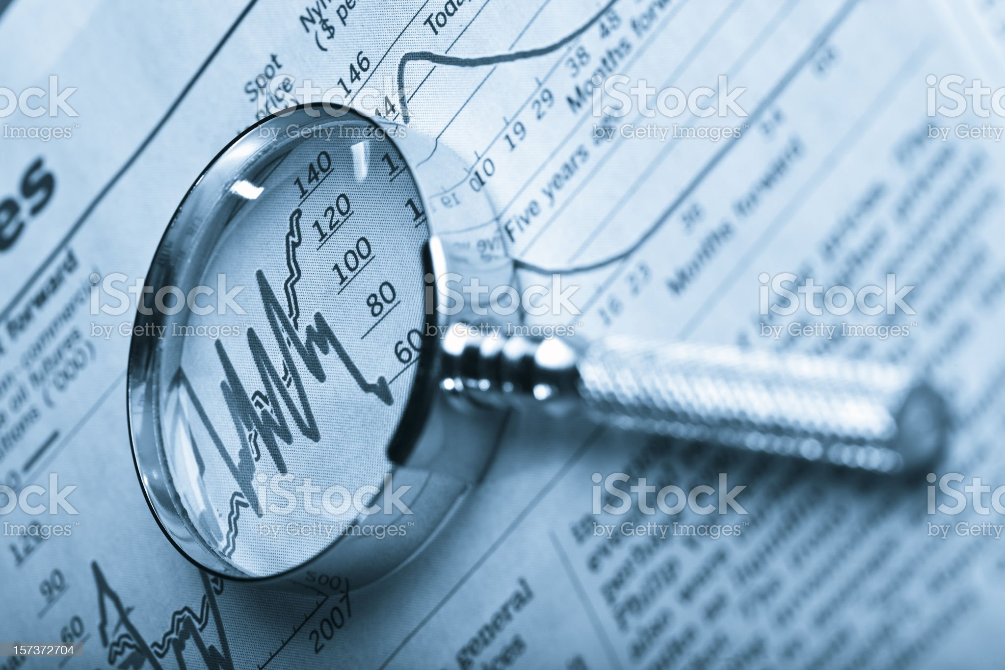 Magnifying glass overs a newspaper graph showing inflation royalty-free stock photo