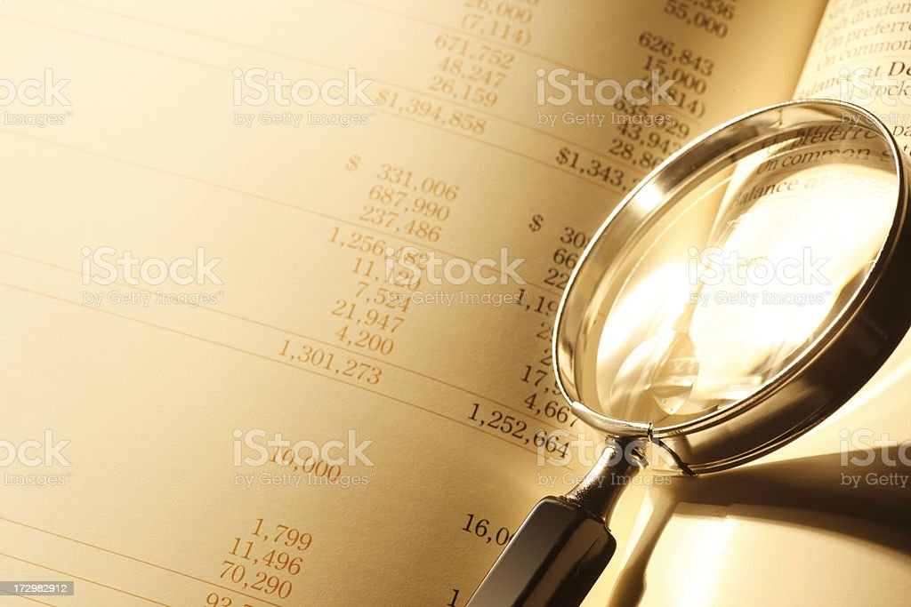Magnifying glass resting on balnce sheet royalty-free stock photo