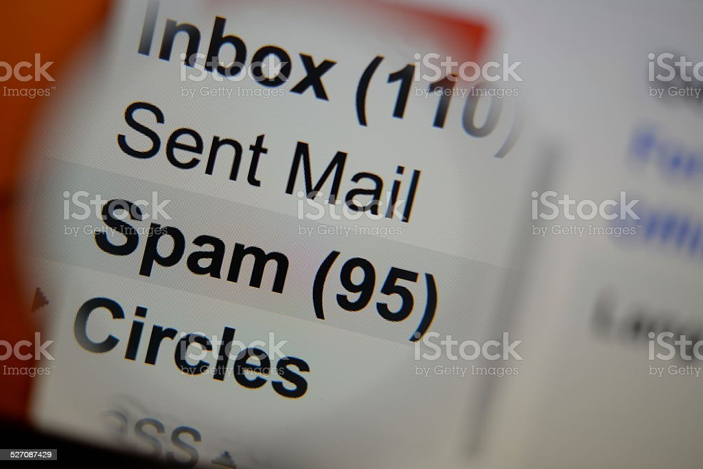Magnifying glass showing a spam folder. stock photo
