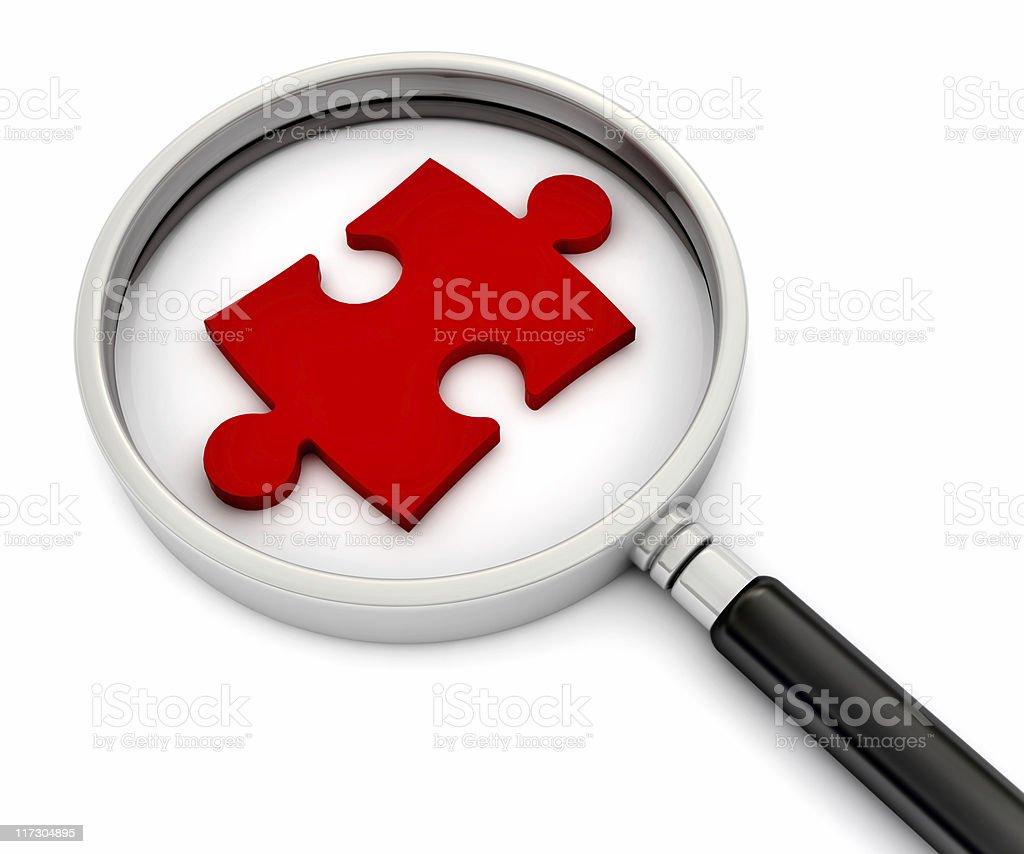 Magnifying glass with a red puzzle piece under it stock photo
