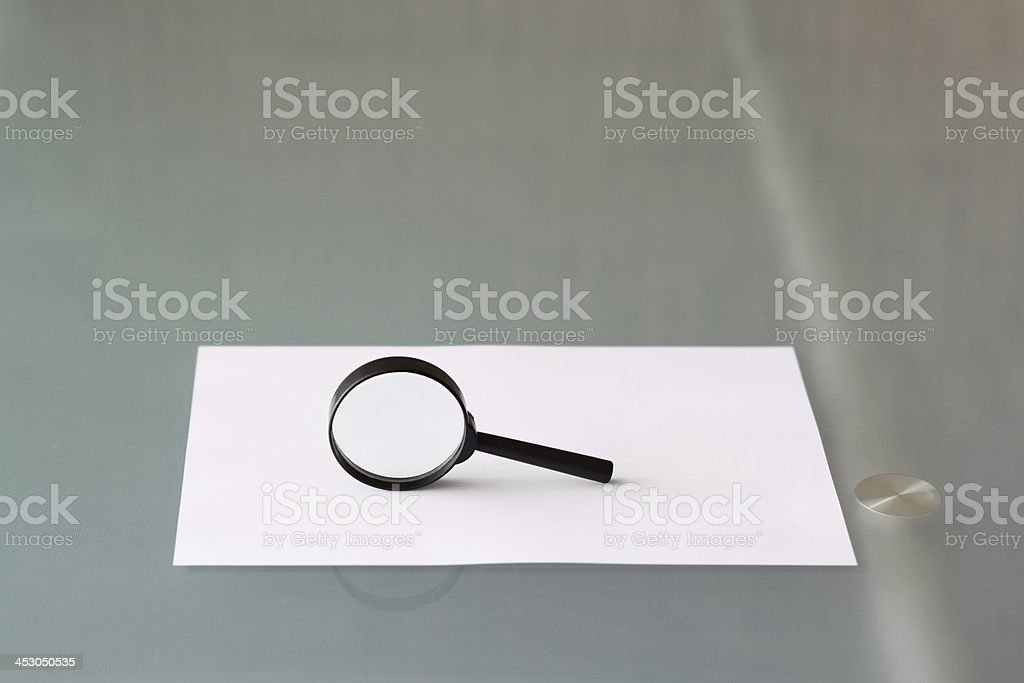Magnifying glass with blank document royalty-free stock photo