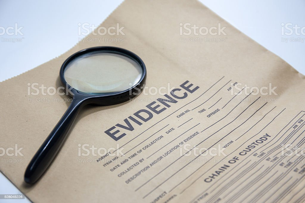magnifying glass with evidence bag stock photo