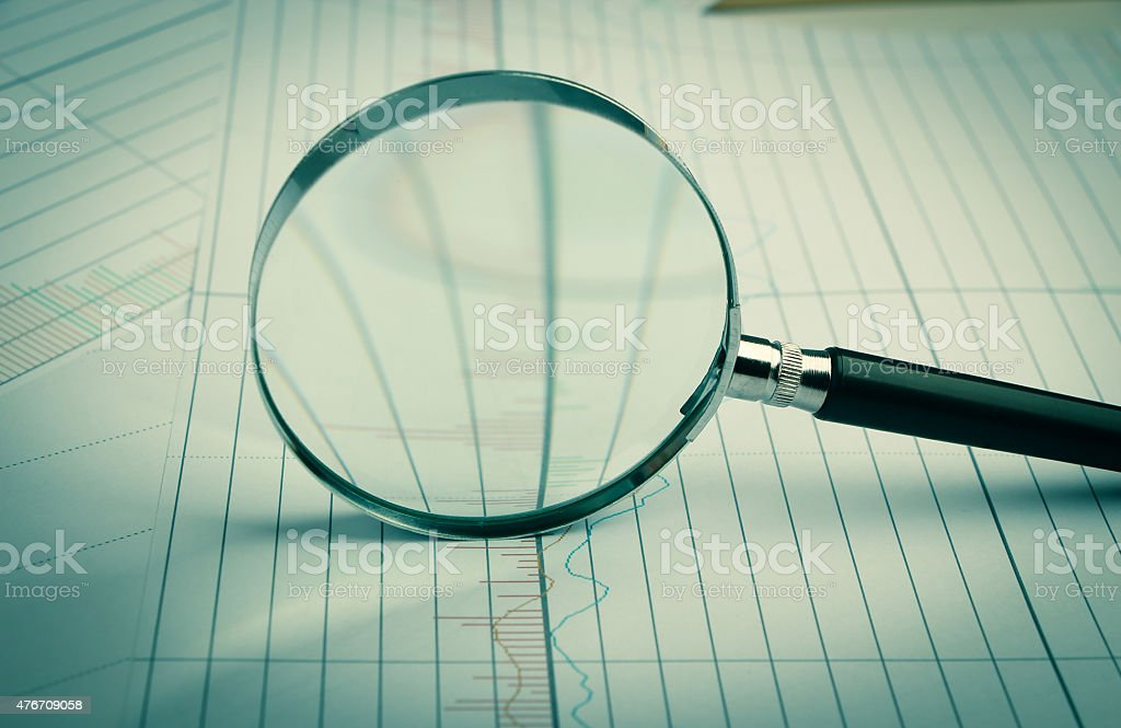 Magnifying glass with financial graph stock photo
