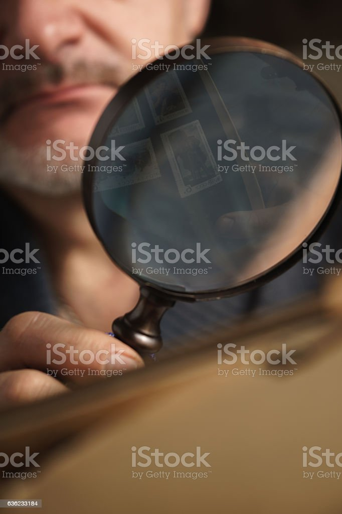 Magnifying glass with reflective stamps in the man`s hand stock photo