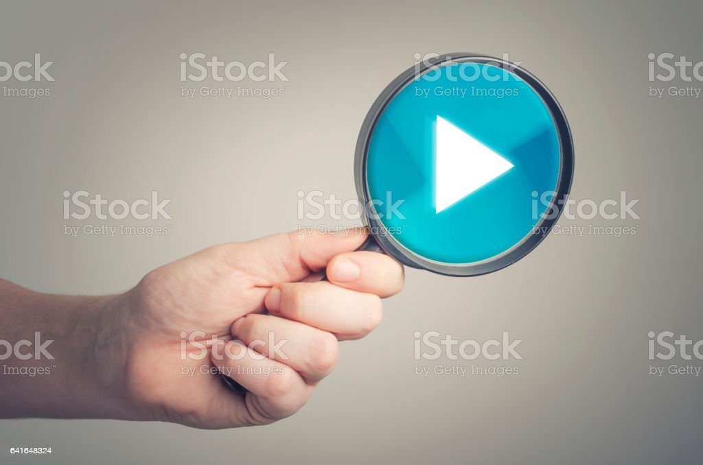 Magnifying glass with the play button icon stock photo