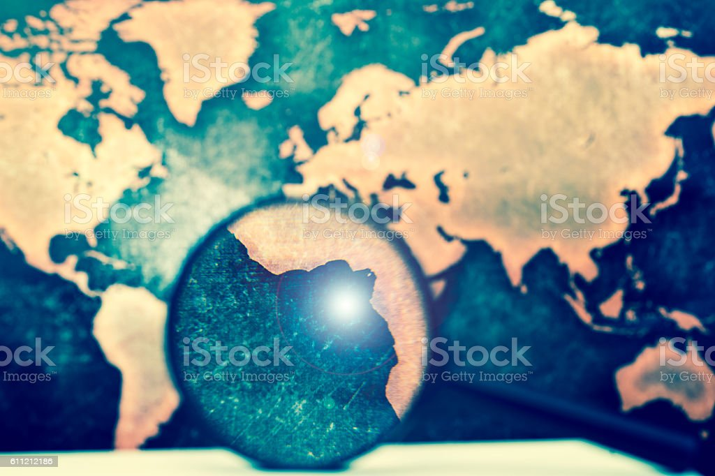 Magnifying lens against grunge world map, with lens flare stock photo