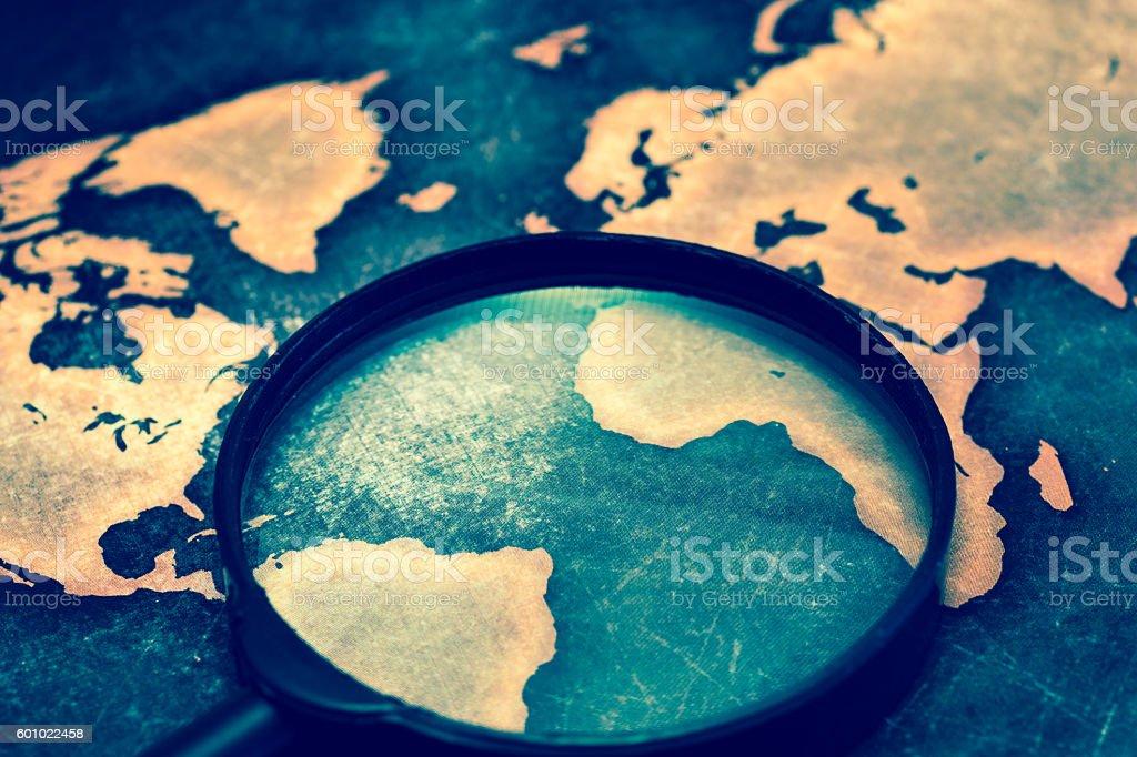 Magnifying lens on grunge world map stock photo