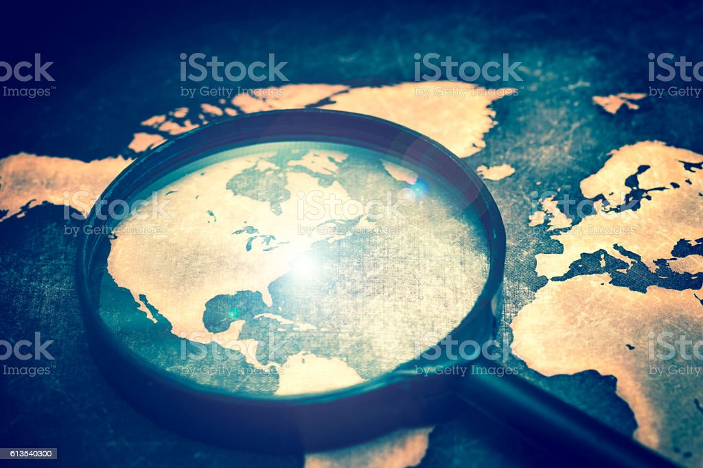 Magnifying lens on grunge world map, with lens flare stock photo