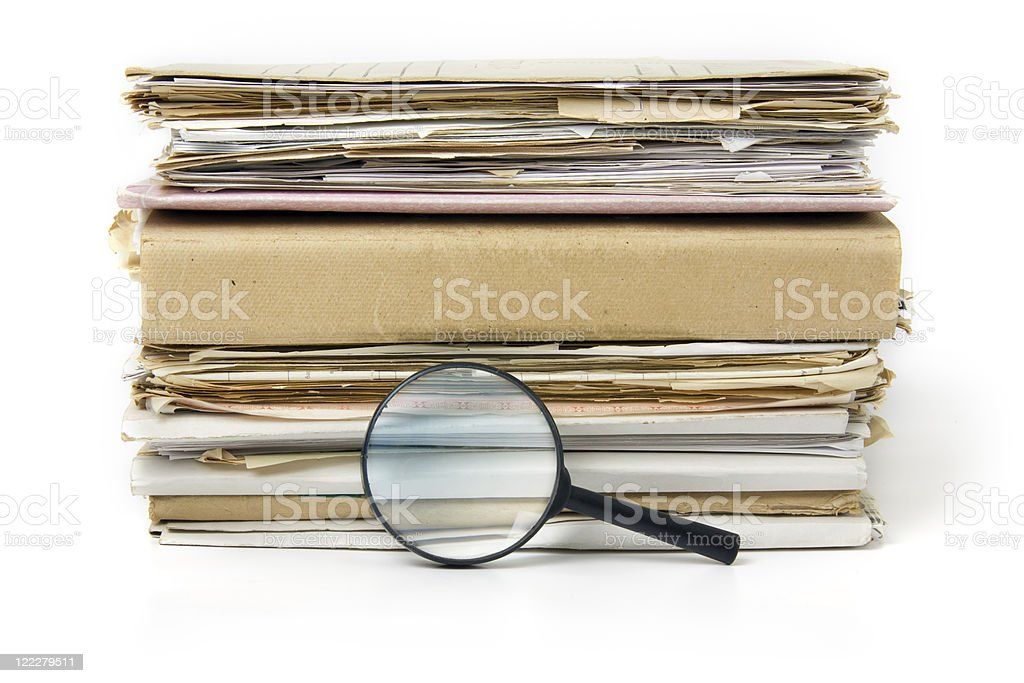 Magnifying lens  on the background of old files stack royalty-free stock photo