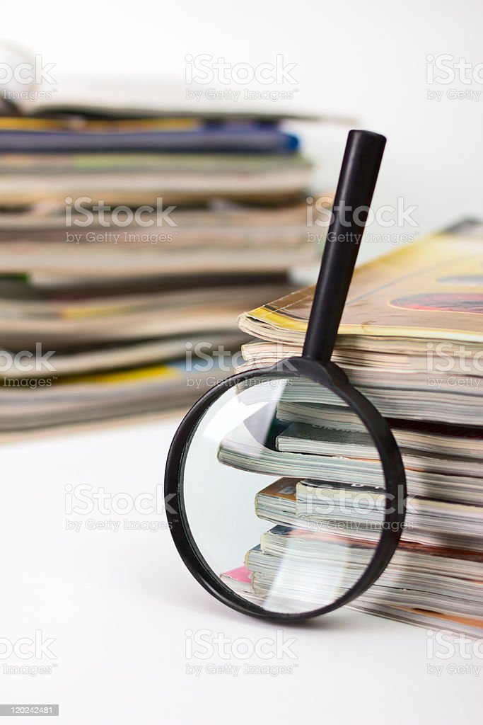Magnifying lens on the stack of magazines background royalty-free stock photo