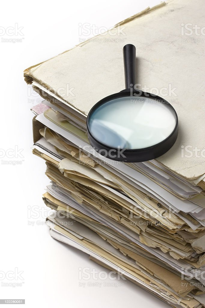 Magnifying lens  on the stack of old paper files royalty-free stock photo