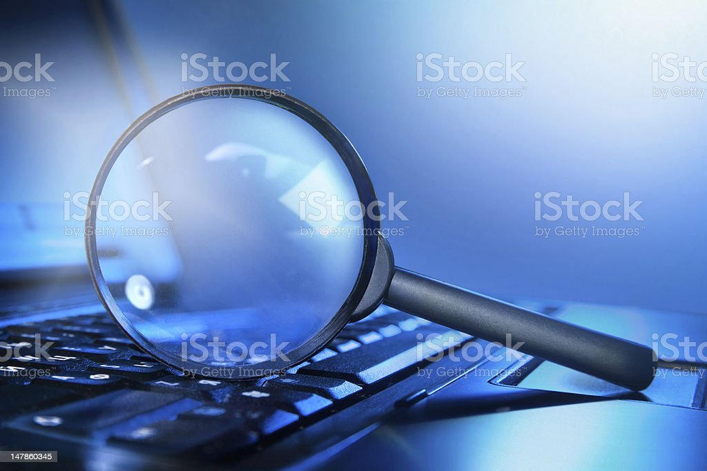 magnifying loupe on the laptop keyboard stock photo