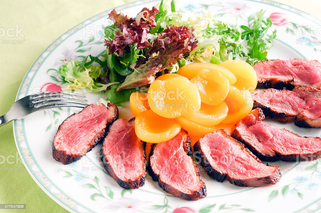 Magret, duck breast, with side salad and peach stock photo