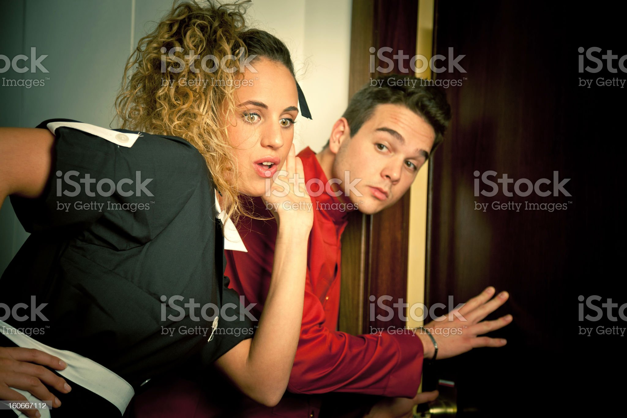 Maid and porter eavesdropping at an hotel door royalty-free stock photo
